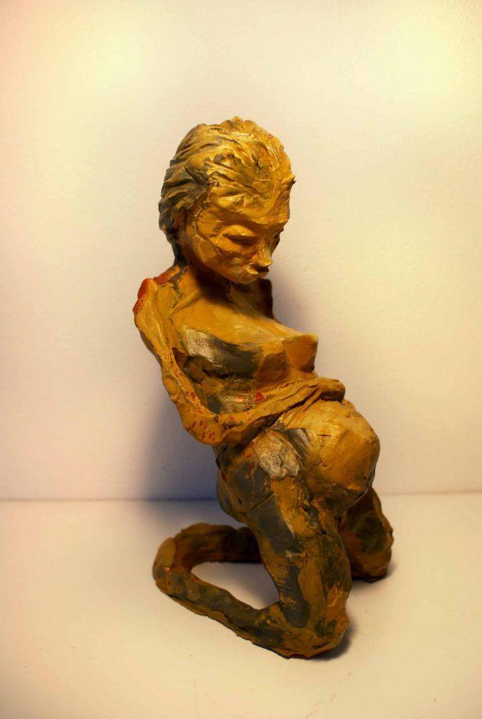 Gul skulptur der viser en gravid